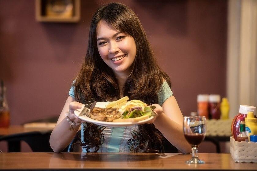 Ung kvinna med mat på restaurang